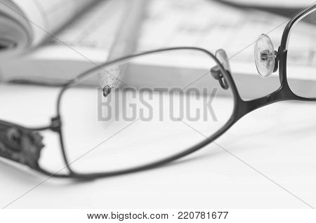 Sharp pencil in focus, eyeglass and crossword close up macro shot in black and white.