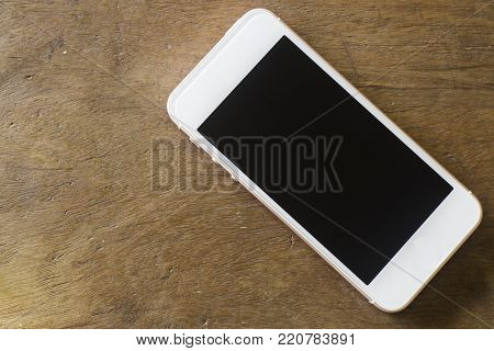 Smart phone with blank screen on wooden table, stock photo