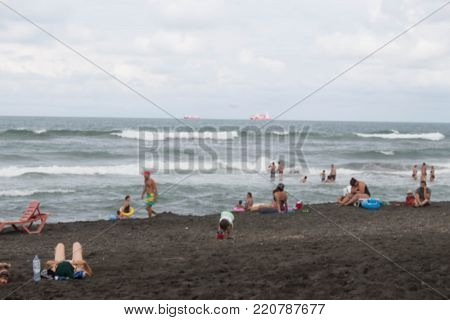 A nasty day. Blurred photo of people on sand beach. Travel or sea vacations concept