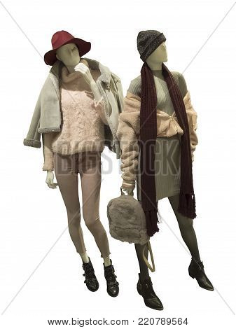Two full-length female mannequins wear warm fashion clothing. Isolated on white background. No brand names or copyright objects.