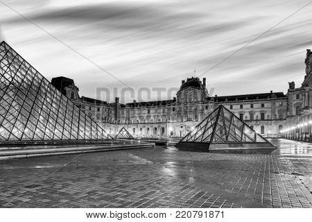 PARIS, FRANCE - DECEMBER 08, 2017: Black and white view of famous Louvre Museum with Louvre Pyramid at evening. Louvre Museum is one of the largest and most visited museums worldwide
