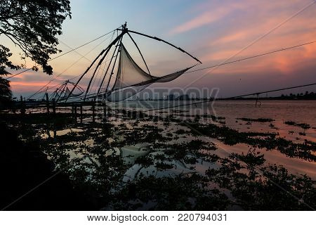 Chinese fishernets at the coast of Kochi during sunset with blue redish sky, India