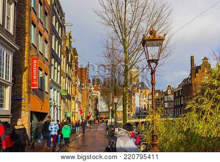 Amsterdam, Netherlands - December 14, 2017: The people going near most famous canals and embankments of Amsterdam city during sunset at Amsterdam, Netherlands on December 14, 2017. General view of the cityscape and traditional Netherlands architecture