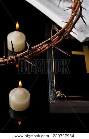 Candles with crown of thorns and Holy Scripture on black background.