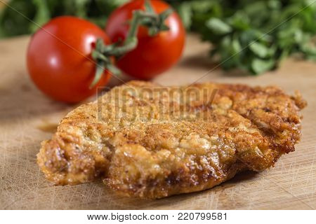 Fried breaded schnitzel (could be either veal, pork or chicken schnitzel) on wood