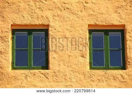 green two windows on orange wall background house fasade architecture detail, scandinavia
