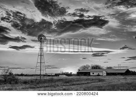 A water-pumping windmill at sunset on a farm near Ritchie in the Northern Cape Province of South Africa. Monochrome
