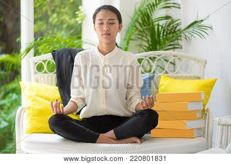 Beautiful young woman meditating while sitting on sofa at home