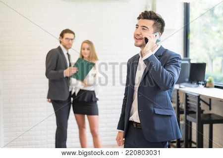 Active and Young Smart Confident Businessman Talking On Phone.Business Freelanc Co-Working Space Luxurious Serviced Office For Rent Concept.