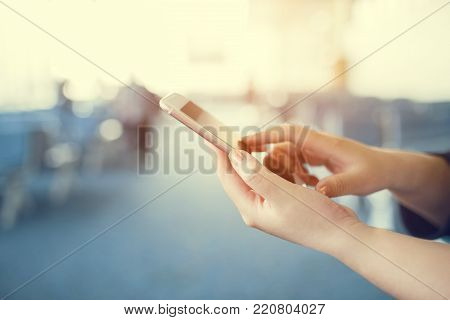 Woman sending message with smartphone. Hands of woman sending SMS via smartphone