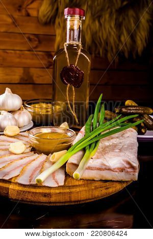 Ukrainian traditional food - salo. Sliced bacon with mustard, garlic, onion on wooden board and vodka bottle