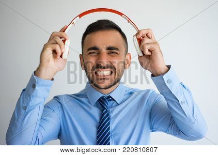 Closeup of frustrated   Caucasian man with clenching teeth putting out headphones. Businessman annoyed with unpleasant sounds from earphones. Irritating and listening concept