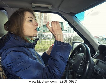 Young fenmale driver driving and drinking water from a bottle