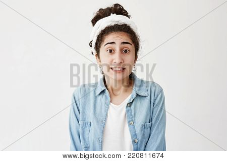 Stressed anxious young casually dressed woman with dark wavy hair and do-rag feeling tension and stress while facing problems, can't stand pressure, clenching white teeth. Body language and face expression, emotions, feelings