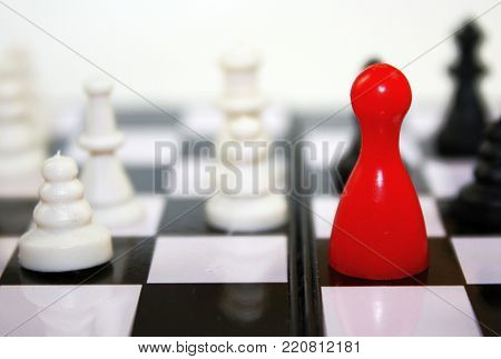 Beautiful black and white contrast with red ludo figure on chessboard. Conceptual leadership game photo.