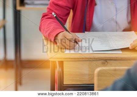 Asian Students holding pencil in hand doing multiple-choice quizzes or testing exams answer sheets exercises with red jacket in secondary school, college university classroom in education concept