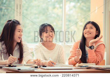Happy Asian young woman doing group study. Asian University or college students studying together with tablet,laptop and documents paper for report near windows in classroom. Education class Concept