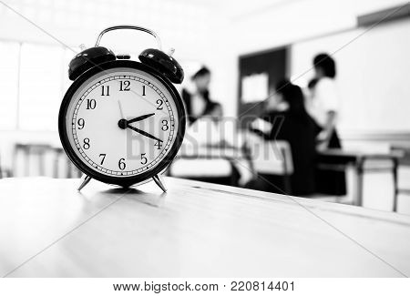 Alam clock located on wood teacher table in final exam room of secondary school, college university classroom students in Asia, Thailand. It show a timeout sign. in secondary school, Education concept
