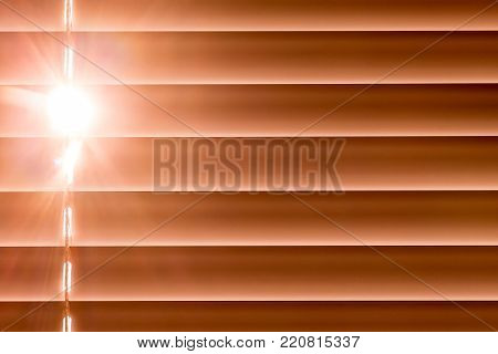 orange horizontal blinds on the window create a rhythm, through the intervals the light passes through