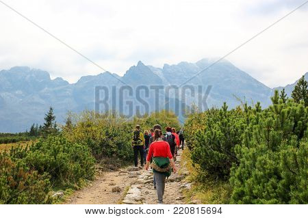 Group of people walking along a trail in the mountains