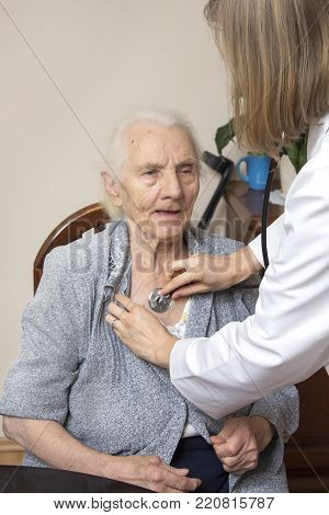 Doctor In White Smock Testing A Very Old Woman With A Stethoscope.
