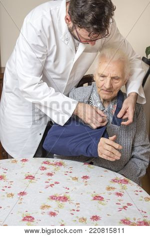 Male Nurse Puts A Sling On The Ill Hand Of An Old Woman.