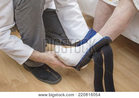 The Male Nurse Assumes An Ankle Stabilizer On The Leg Of An Old Woman.
