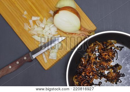 Spoiled unhealthy overcooked burned meal. An overhead photo of burnt onion on the black teflon pan. Onion disgusting leftovers. Messthetics aesthetic concept. Fried bad taste fat food for recycling