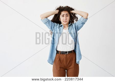 Stressed puzzled young casually dressed girl with hands in dark wavy hair feeling tension and stress while facing problems, can't stand pressure, clenching teeth. Body language