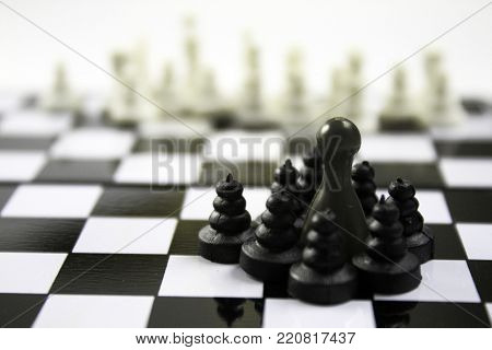 Black and white chessboard chess game photo. Black ludo figure as a leader of black team.