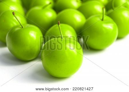 most notable green sour plums, mouth watering sour plums, white background sour plums,