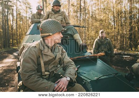 Gomel, Belarus - April 23, 2017: Unidentified Re-enactors Dressed As Soldiers Of United States Of America Infantry And Soviet Russian Red Army Soldier Of World War II Sitting Together In Car BA-64