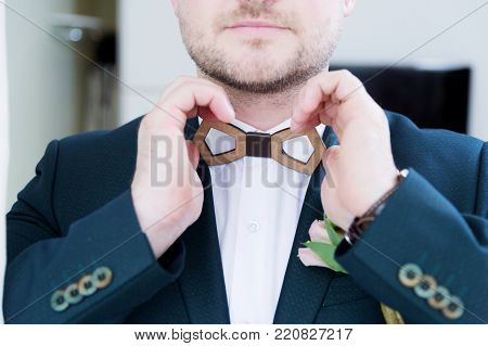 A sturdy newlywed with a beard in a suit adjusts the wooden bow tie on the collar with his white shirt. Super close-up. The concept of business style on holidays