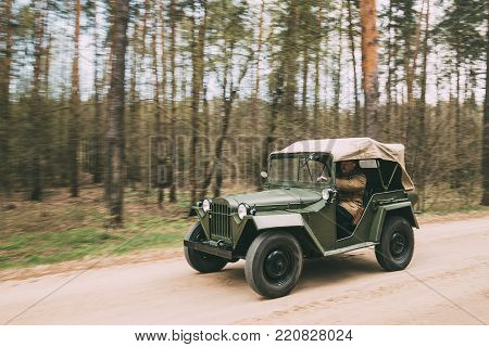 Gomel, Belarus - April 22, 2017: Re-enactor Dressed As Russian Soviet Officer Soldier Driver Of World War II Sitting In Four-wheel Drive Army Truck GAZ-67 Car Of WWII Is Driving Along Forest Road