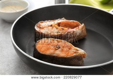 Tasty rainbow trout steaks on frying pan, closeup