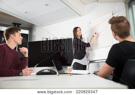 Young businesswoman explaining graph on flipchart to male colleagues in office