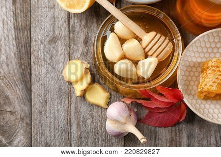 Composition with honey and garlic as natural cold remedies on wooden background, top view