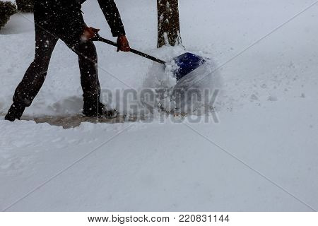 Man shoveling snow from the sidewalk in front of his house after a heavy snowfall in a city Man Removing Snow with a Shovel
