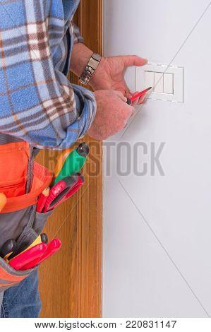 Electrician's hands assembles a standard bipolar wall socket.