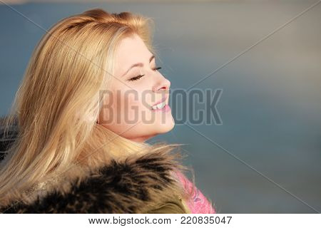 Leisure, spending free time outside, healthy walks concept. Woman wearing warm jacket relaxing outside enjoying beautiful weather, cold sunny day