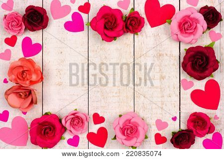 Valentines Day frame of red and pink paper hearts and roses against a rustic white wood background with copy space.