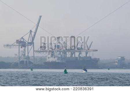 SHIP IN A SEAPORT - Transshipment terminal in the morning fog