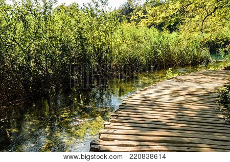 landscape of plitvice lake national park at sunset with water and a wooden path, unesco heritae site, plitivce croatia.