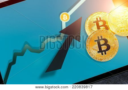 Bitcoin cryptocurrency chart on tablet pc with arrow pointing up. Increasing value and financial upswing concept. Success and gains in crypto bitcoin investments. Copyspace for text.
