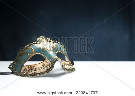 Blue venetian mask on white table with blue background and copy space
