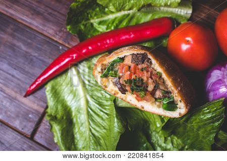 A close-up of a filling of a baked patty. Baked patty on a salad leaf. Tomatoes and onions lie near the lettuce leaf. Chili is on a salad leaf. The sandwich lies on the salad sheet.