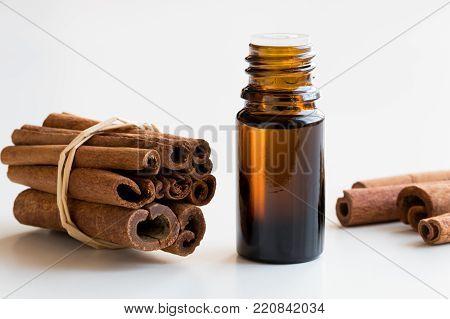 A dark bottle of cinnamon essential oil with cinnamon sticks on white background