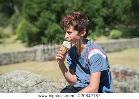 Boy obviously enjoying his ice cream  outdoors on summer day