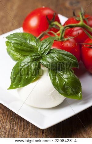 Mozarella, Basil And Tomatoes On A Plate On Wood