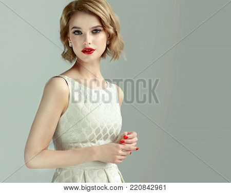 poster of Beautiful model girl with short curly  hair and red lips . Red manicure on nails .Beauty and esthetic care